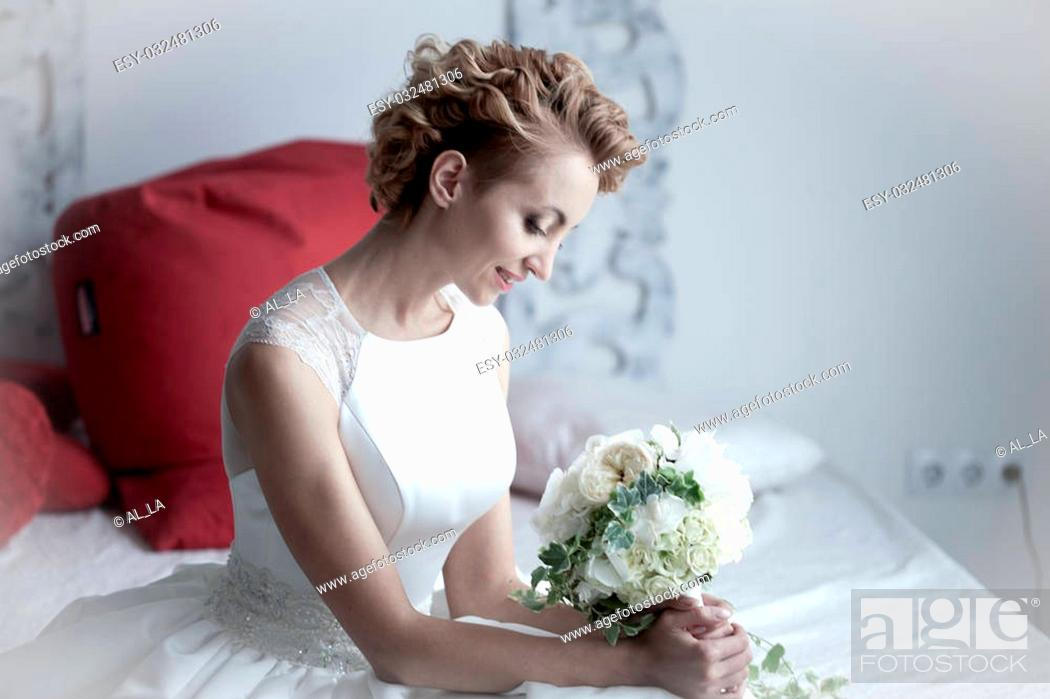 Imagen: charming beautiful bride holding wedding bouquet in her hands. bride in white dress in a luxury interior lying on the beautiful white bed.