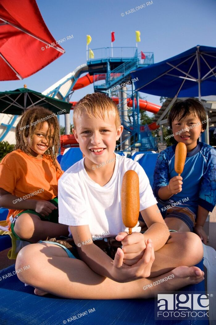 Imagen: Multi-ethnic boys at water park in summer eating corn dogs.