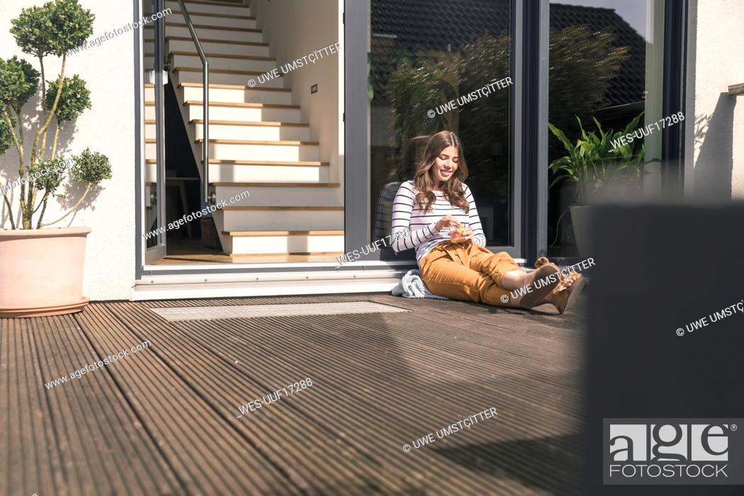 Photo de stock: Young woman sitting on terrace at home.