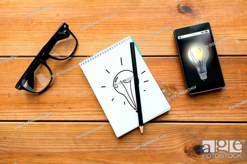 Stock Photo: education, business, idea and technology concept - close up of light bulb drawing in notepad with pencil, smartphone and eyeglasses on wooden table.