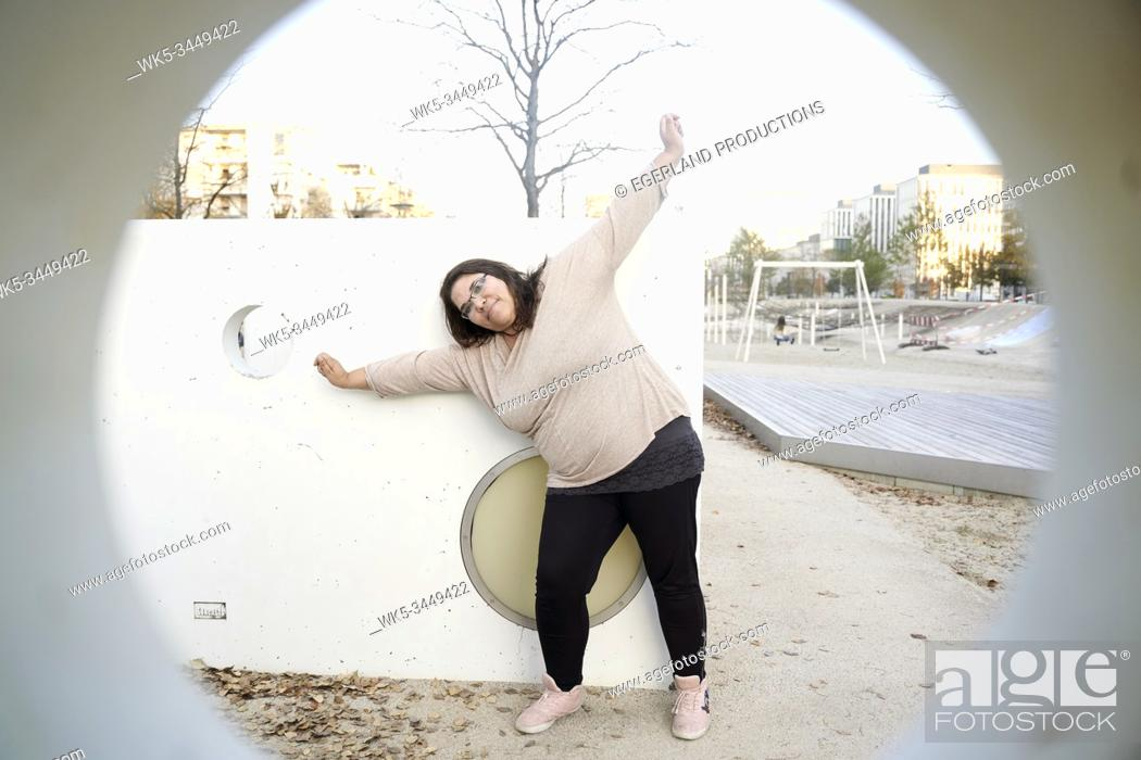 Imagen: playful woman stretching in park.