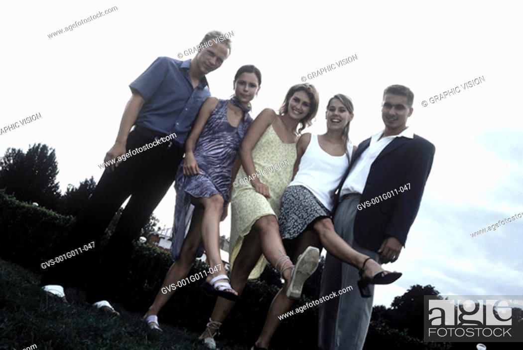 Stock Photo: Portrait of a group of young women showing their legs with young men standing besides them.
