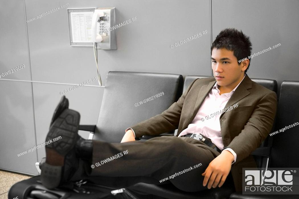 Stock Photo: Businessman reclining on a bench at an airport.