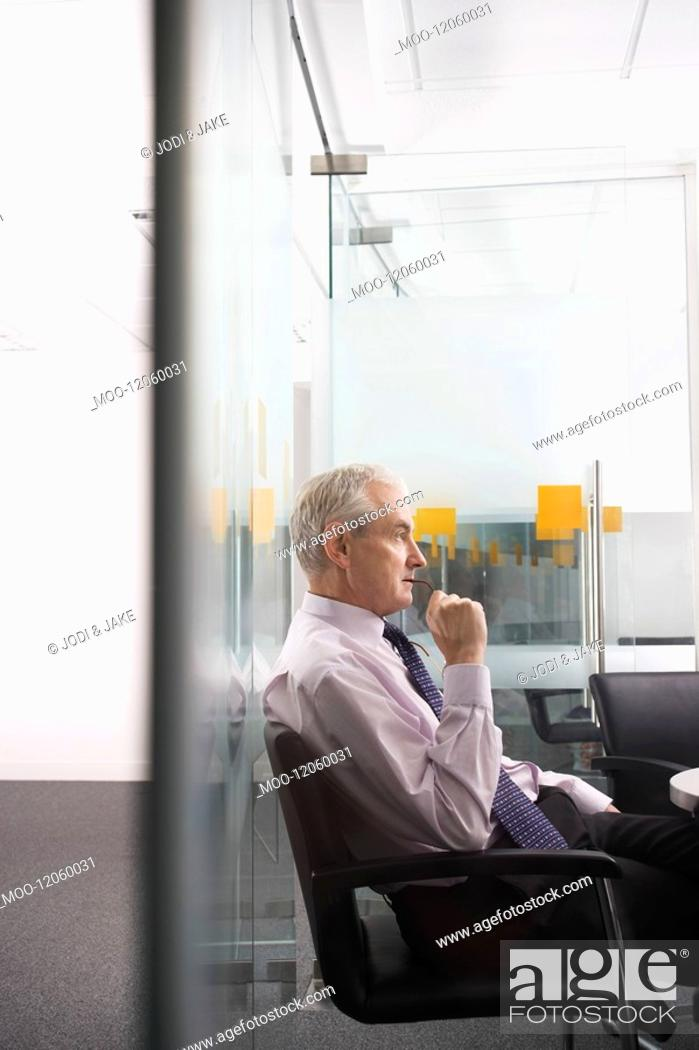 Stock Photo: Mature businessman sitting in conference room side view.