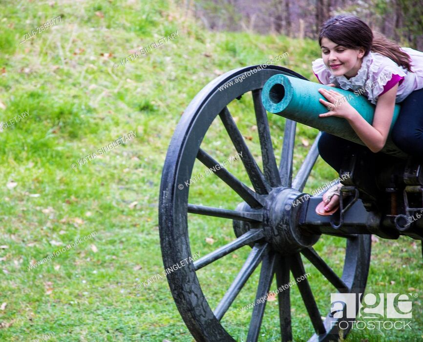 Stock Photo: Old fashion brown wheels with green canon in the middle of an old war field with a preteen laying on it and smiling.