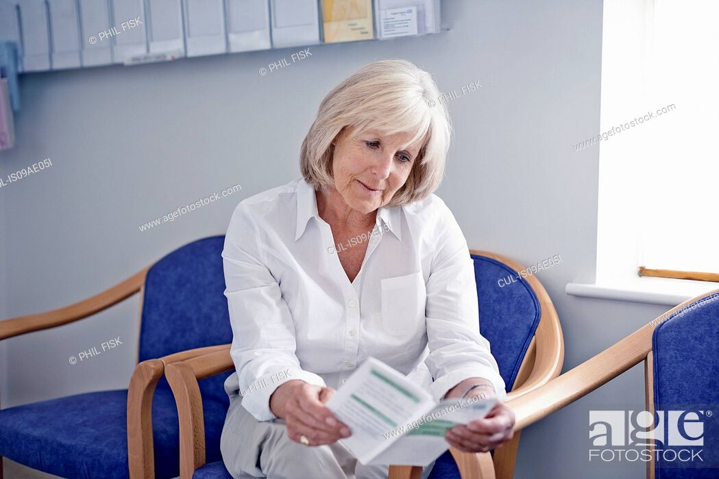 Stock Photo: Mature female patient reading leaflet in hospital waiting room.