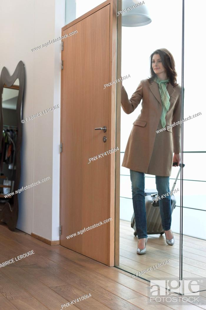 Stock Photo: Woman arriving at home from vacations.