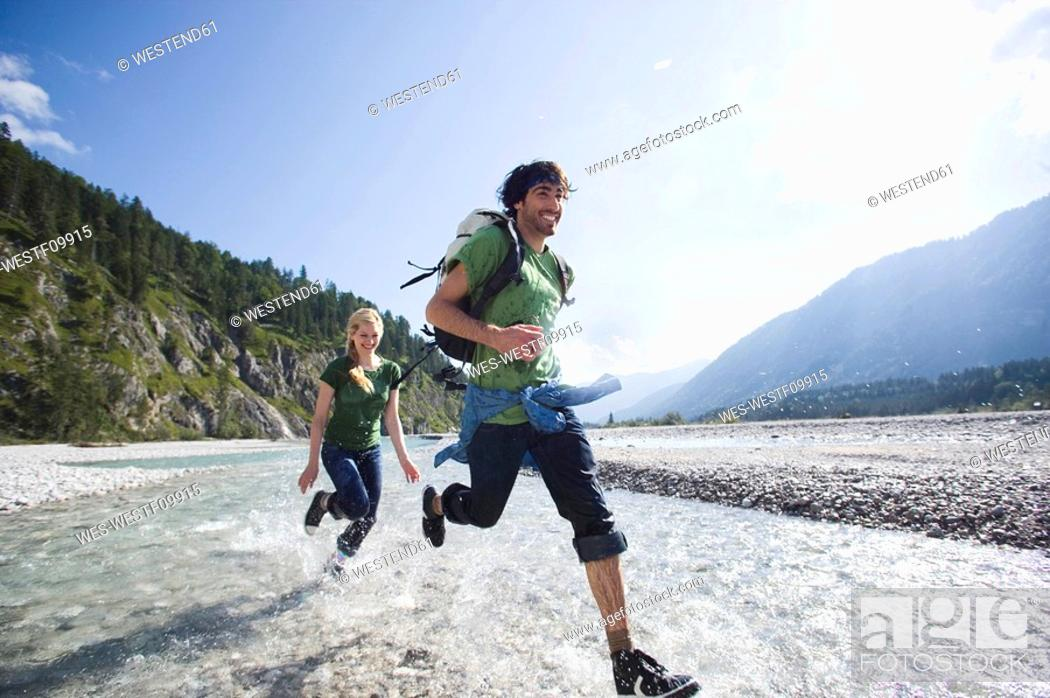 Stock Photo: Germany, Bavaria, Tölzer Land, Young couple running through river.