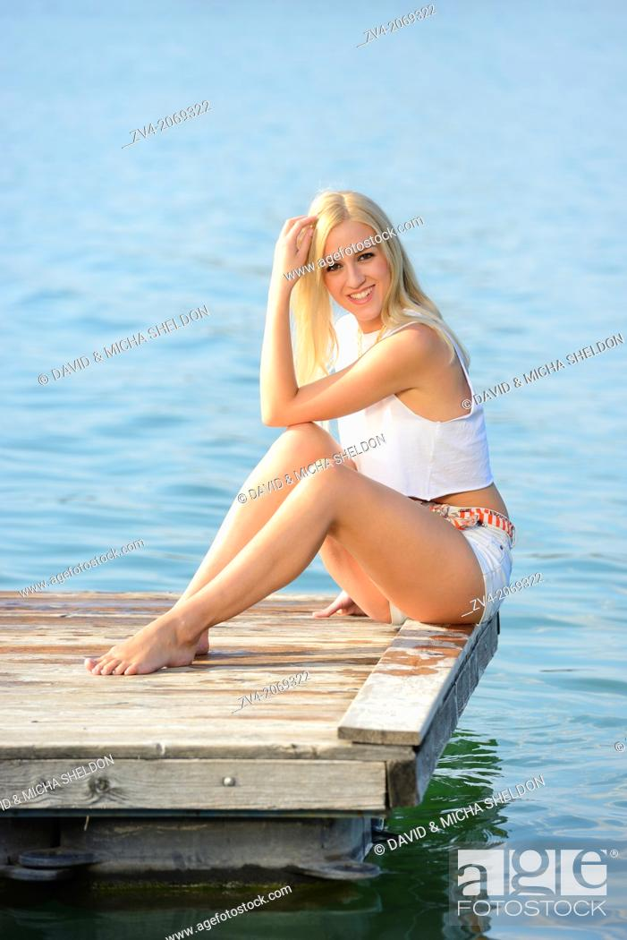 Stock Photo: Young woman sitting on a jetty at a lake in Austria.