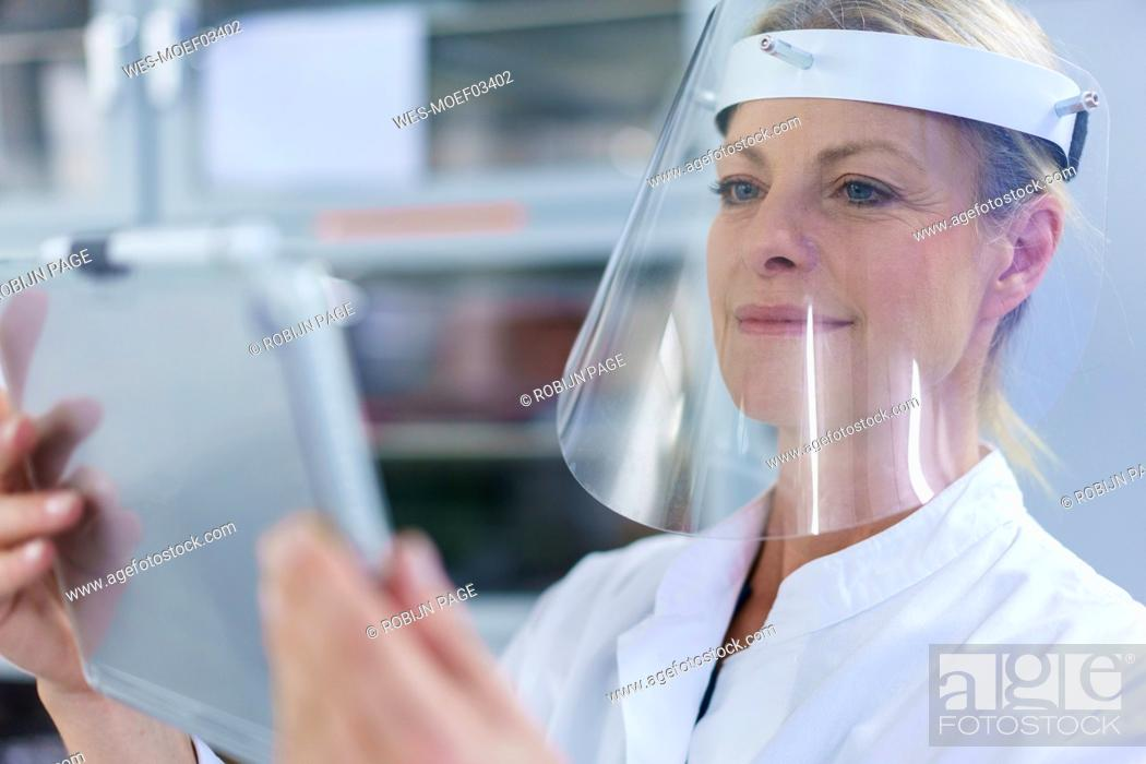 Imagen: Mature female scientist wearing protective face shield while using digital tablet at laboratory.