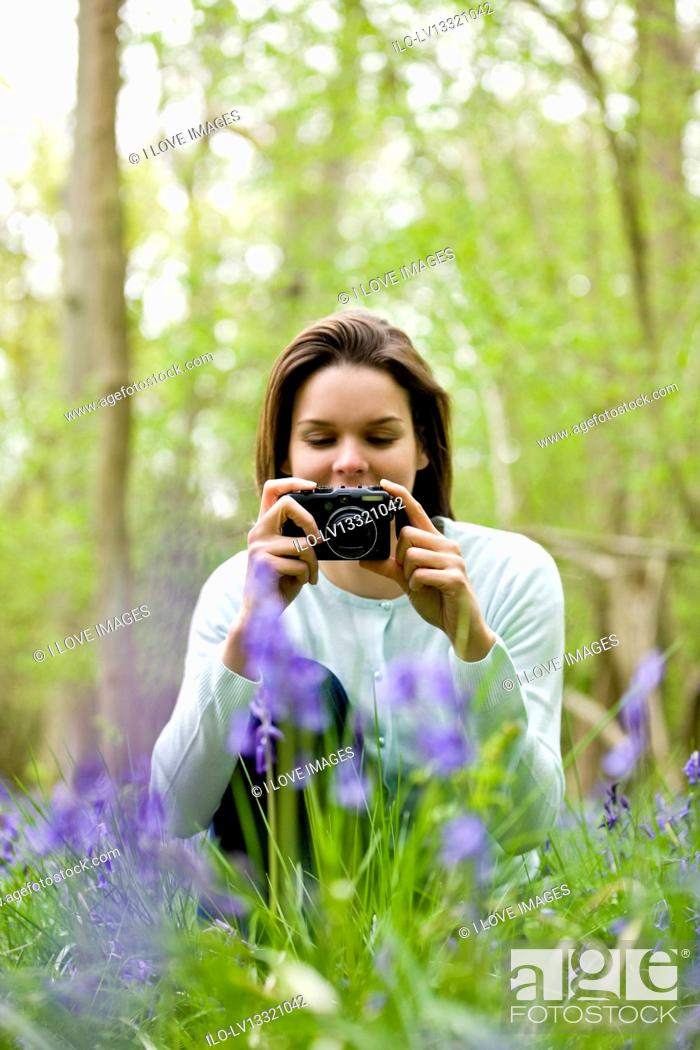 Stock Photo: A young woman photographing bluebells.