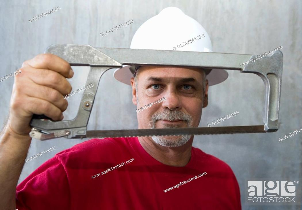 Stock Photo: Portrait of a mature man holding a coping saw.