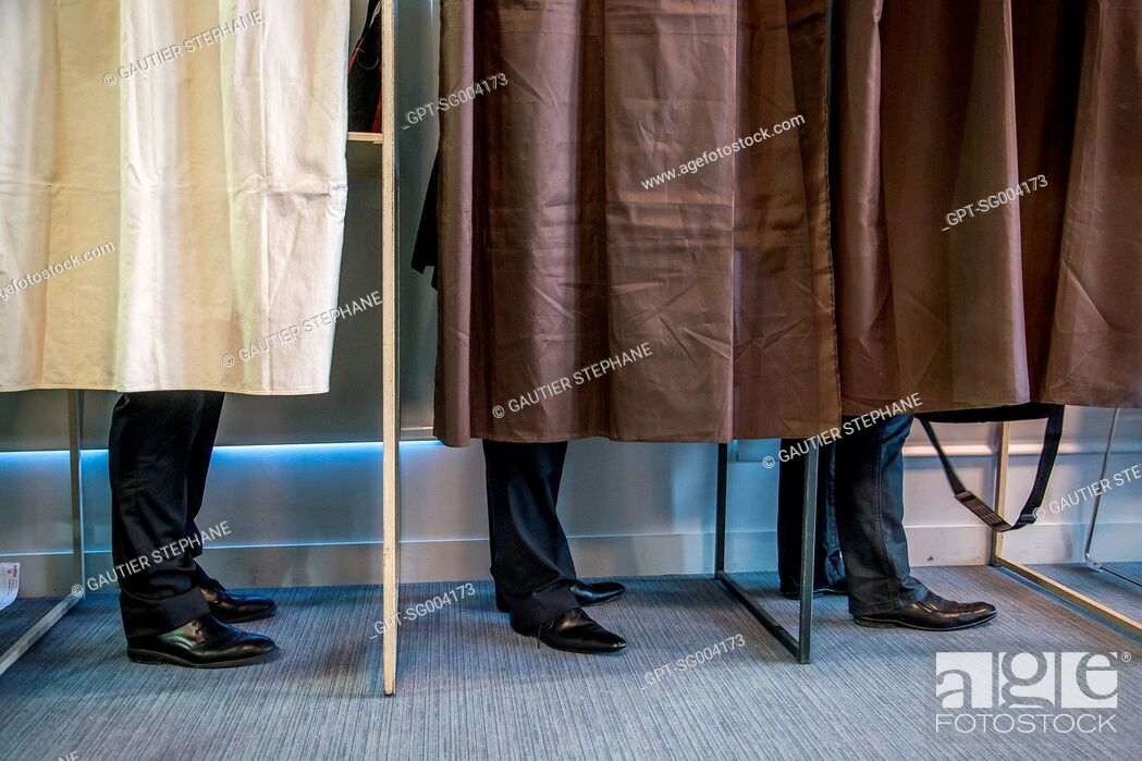 Stock Photo: VOTERS IN A VOTING BOOTH, POLLING STATION.
