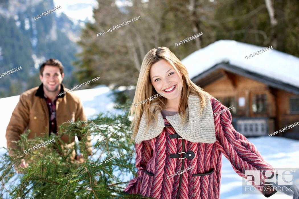 Stock Photo: Portrait of smiling couple carrying fresh cut Christmas tree in snow.