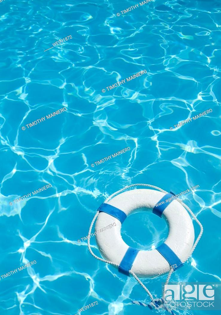 Stock Photo: Life ring floating on top of sunny blue water.