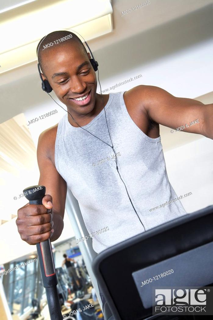 Stock Photo: Sweaty man on elliptical machine in health club listening to headphones.