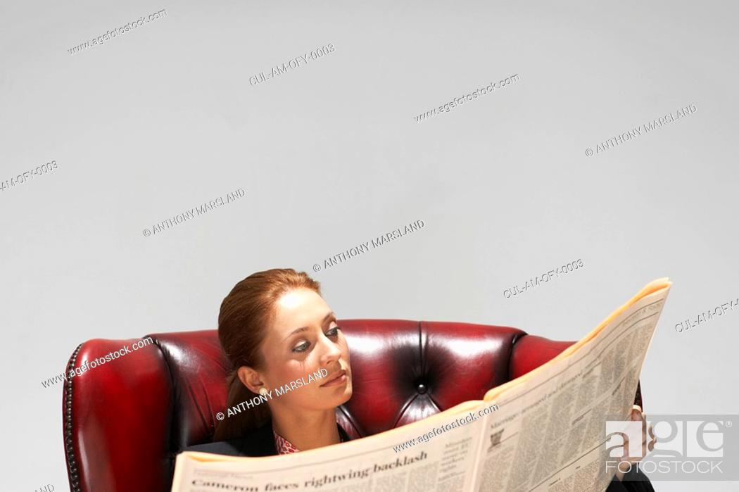 Stock Photo: Businesswoman in a comfy leather chair with newspaper.
