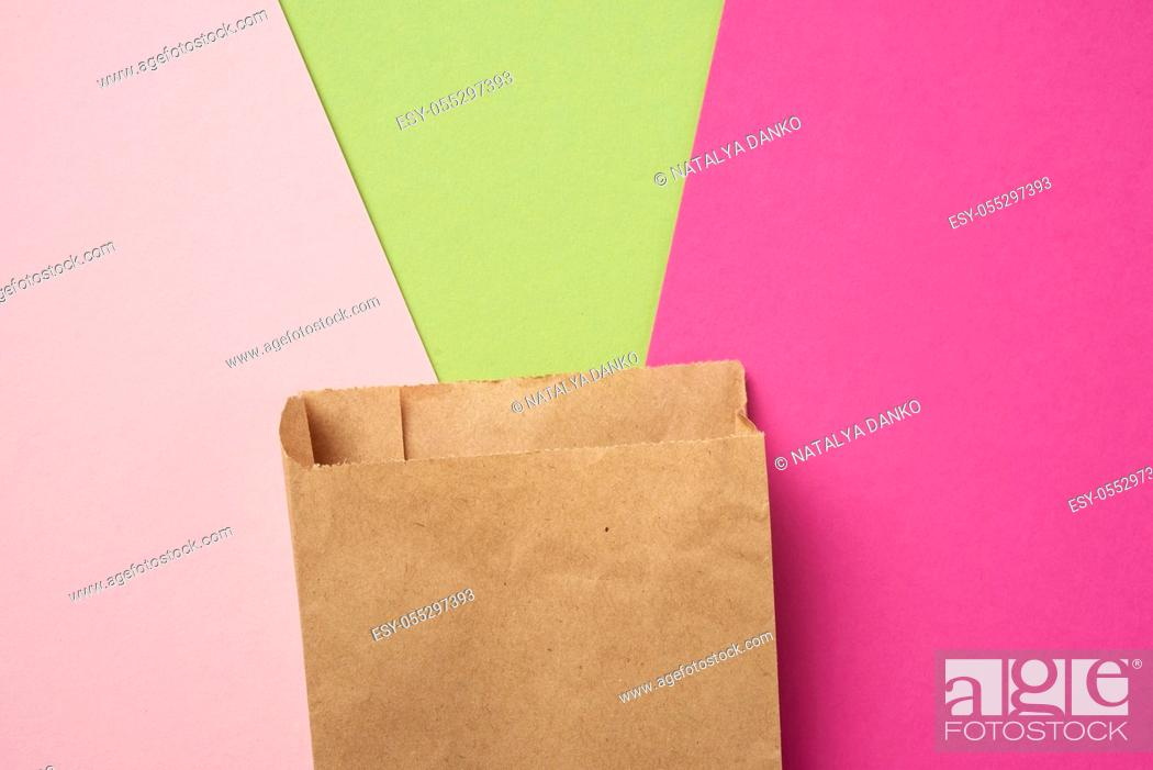 Stock Photo: brown paper disposable food bag on a pink background, concept of delivery and ordering, top view.