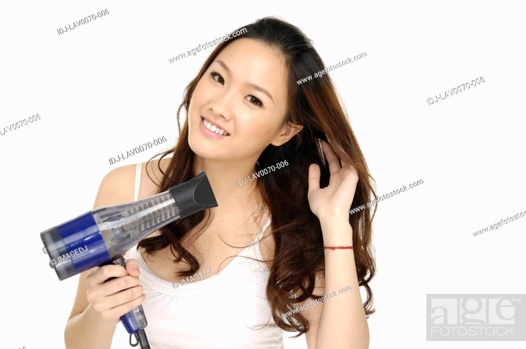 Stock Photo: Portrait of young woman using a hair dryer.