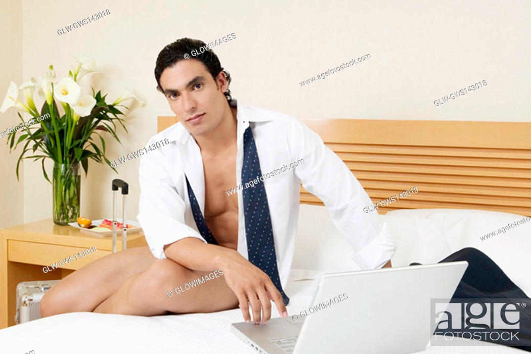 Stock Photo: Portrait of a young man sitting on the bed with a laptop.