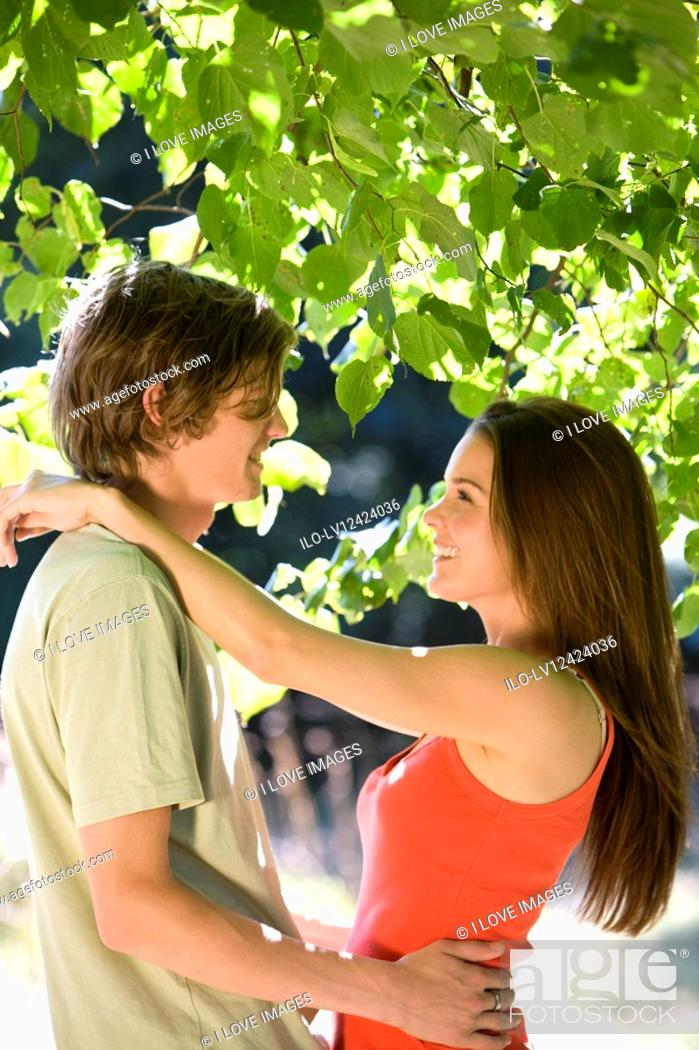 Stock Photo: A young couple embracing under a tree.