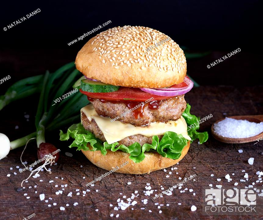 Imagen: fresh homemade burger with lettuce, cheese, onion and tomato on a rustic wooden board.