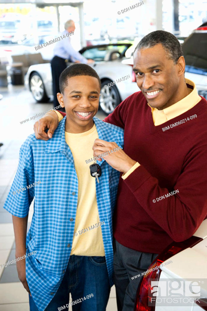 Stock Photo: Father and son at a car dealership.