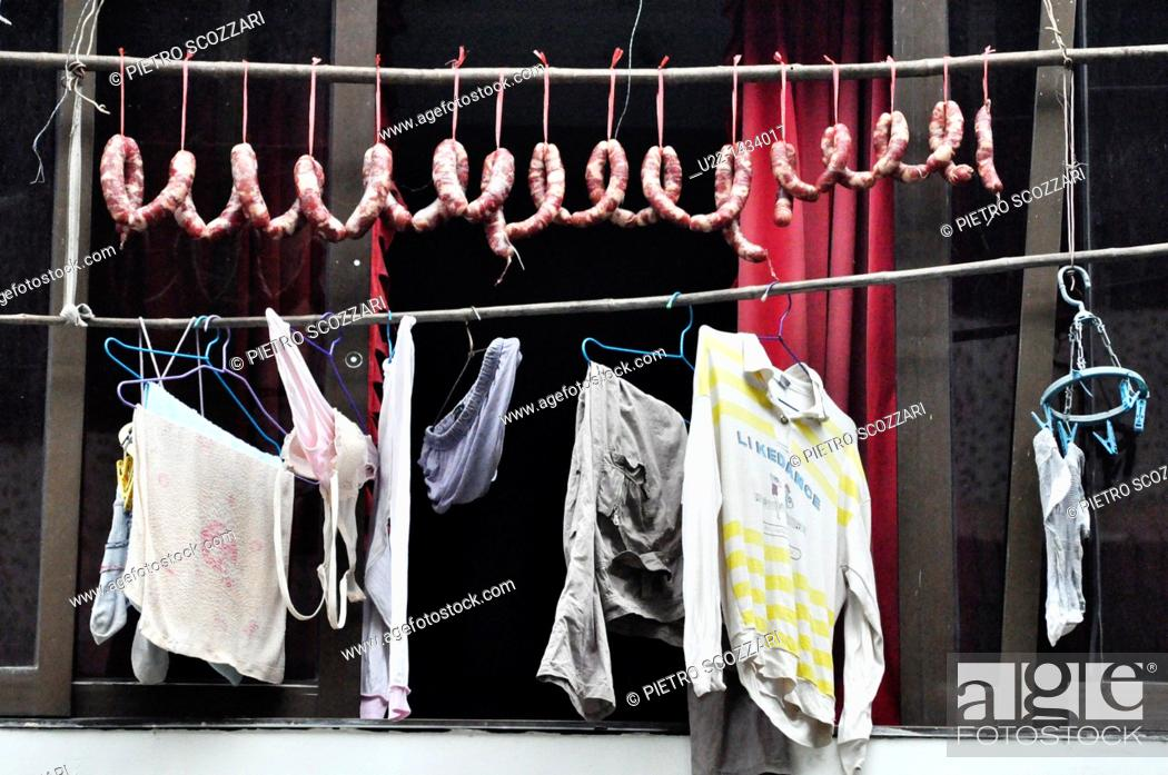Stock Photo: Yangshou (China): sausages and laundry drying by a window.