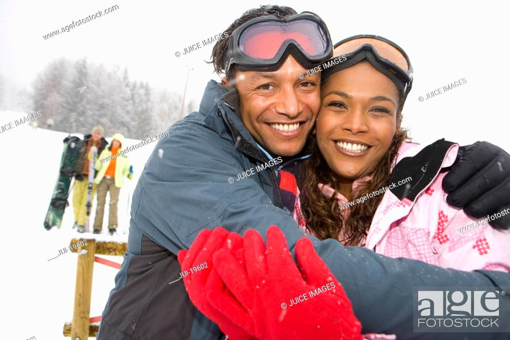 Stock Photo: Mixed race couple hugging in winter setting, couple in background.