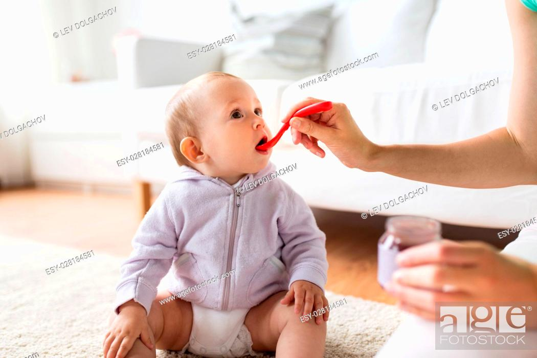 Stock Photo: family, food, child, eating and parenthood concept - mother with puree and spoon feeding little baby at home.