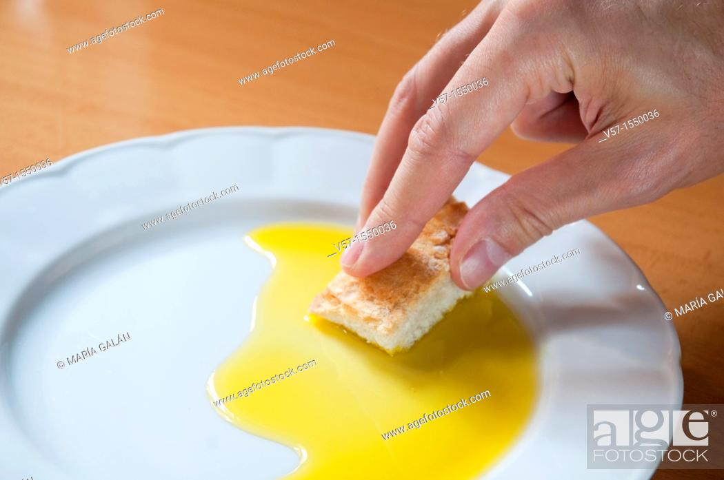 Stock Photo: Man's hand dipping bread in olive oil. Close view.