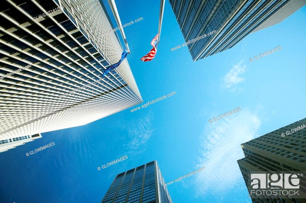 Stock Photo: Low angle view of two flags with skyscrapers, New York City, New York State, USA.