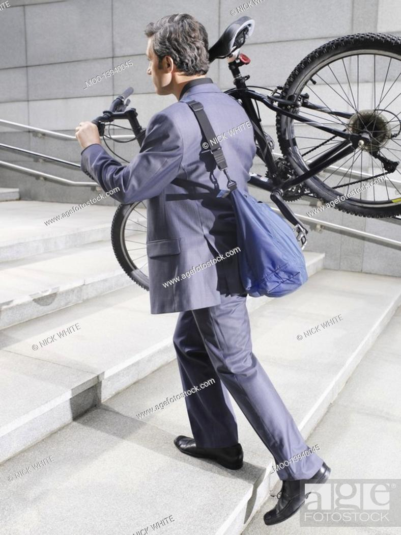 Stock Photo: Business man carrying bicycle up steps side view.