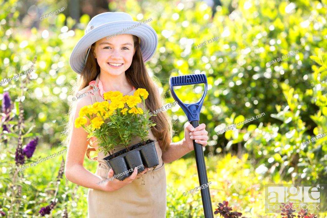 Stock Photo: Caucasian girl holding tray of flowers in garden.