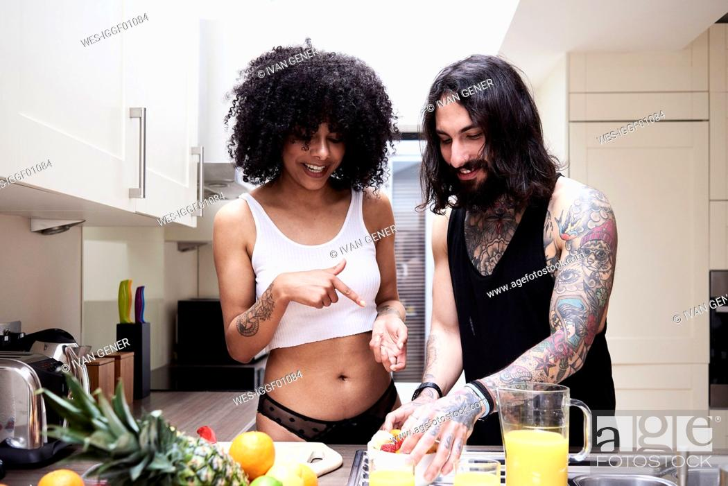Stock Photo: Happy young couple preparing healthy meal in kitchen.