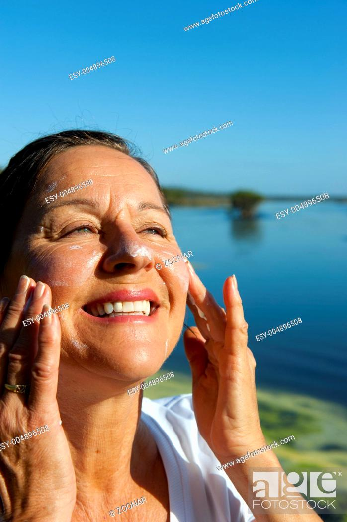 Stock Photo: Woman Skin cancer protection suncream.