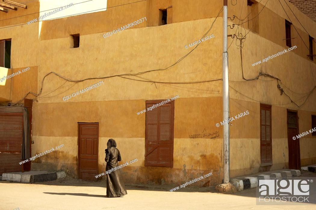 Stock Photo: Muslim Woman with Camera Standing near Shuttered Building on Street Corner, Luxor, Egypt.