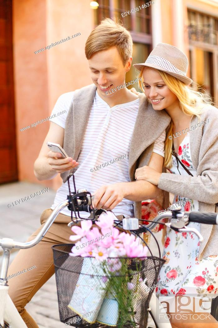 Stock Photo: summer holidays, bikes, love, relationship, navigation, gps and dating concept - couple with bicycles and smartphone in the city.
