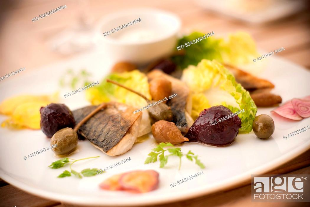 Stock Photo: Plate of fish with salad and olives.