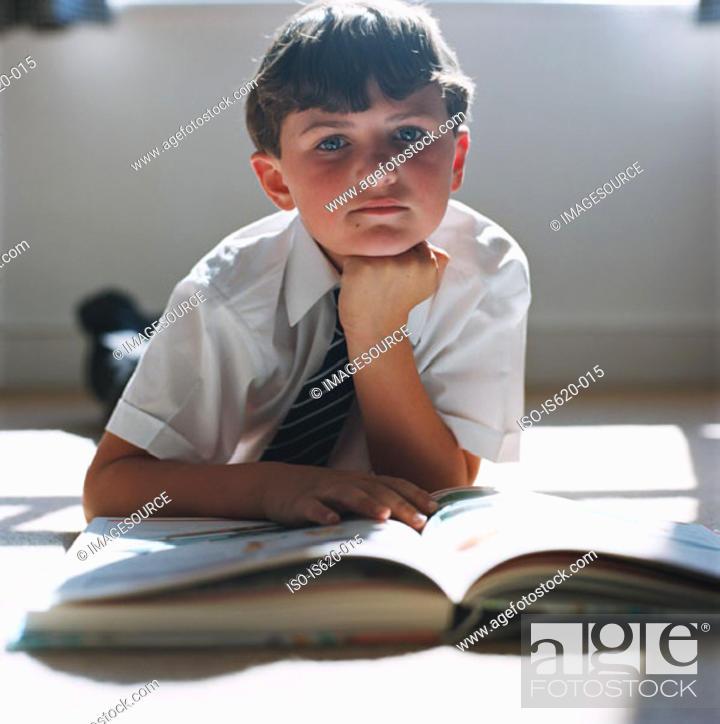 Stock Photo: Boy doing homework on floor.