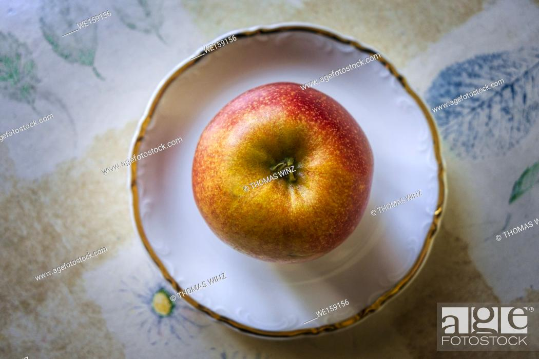 Stock Photo: Beautiful glowing apple on a plate , Kitchen table with Tablecloth.