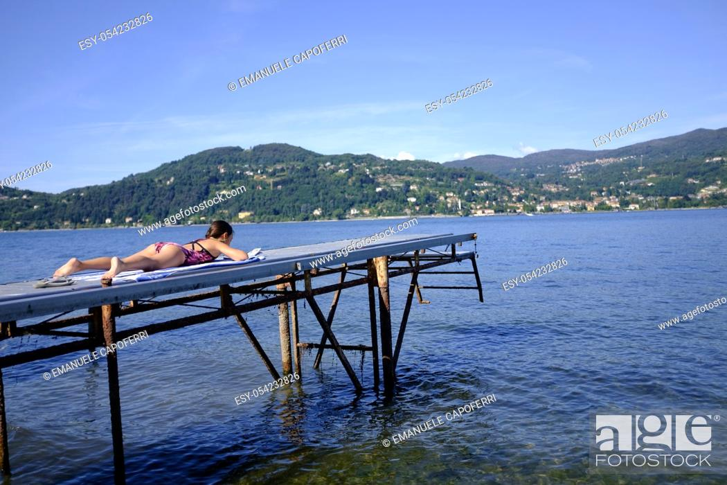 Stock Photo: Little girl on the pier, Lake Maggiore, Ranchi, Lombardy, Italy.