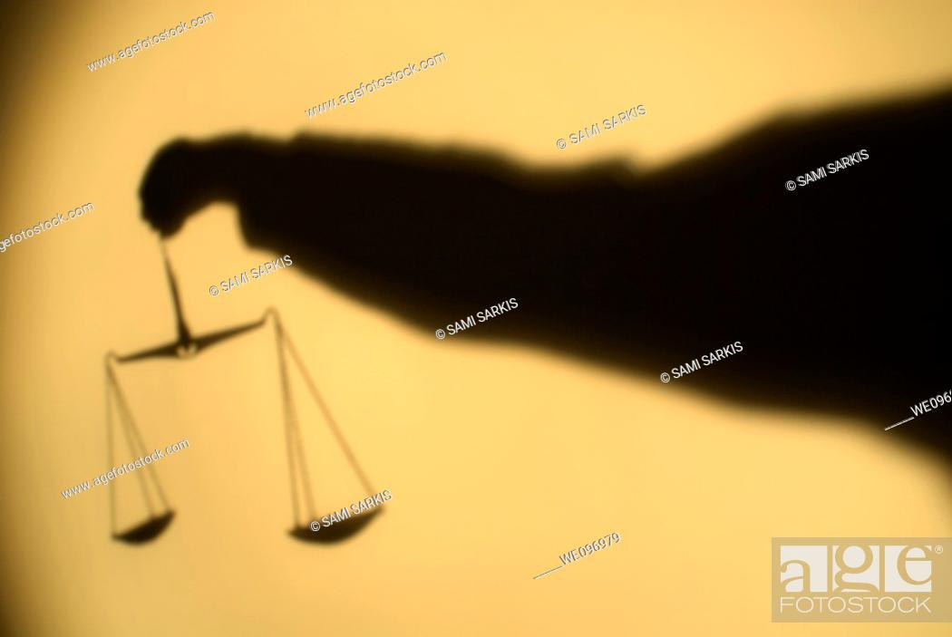 Stock Photo: Shadow of a person's arm holding out the Scales of Justice.