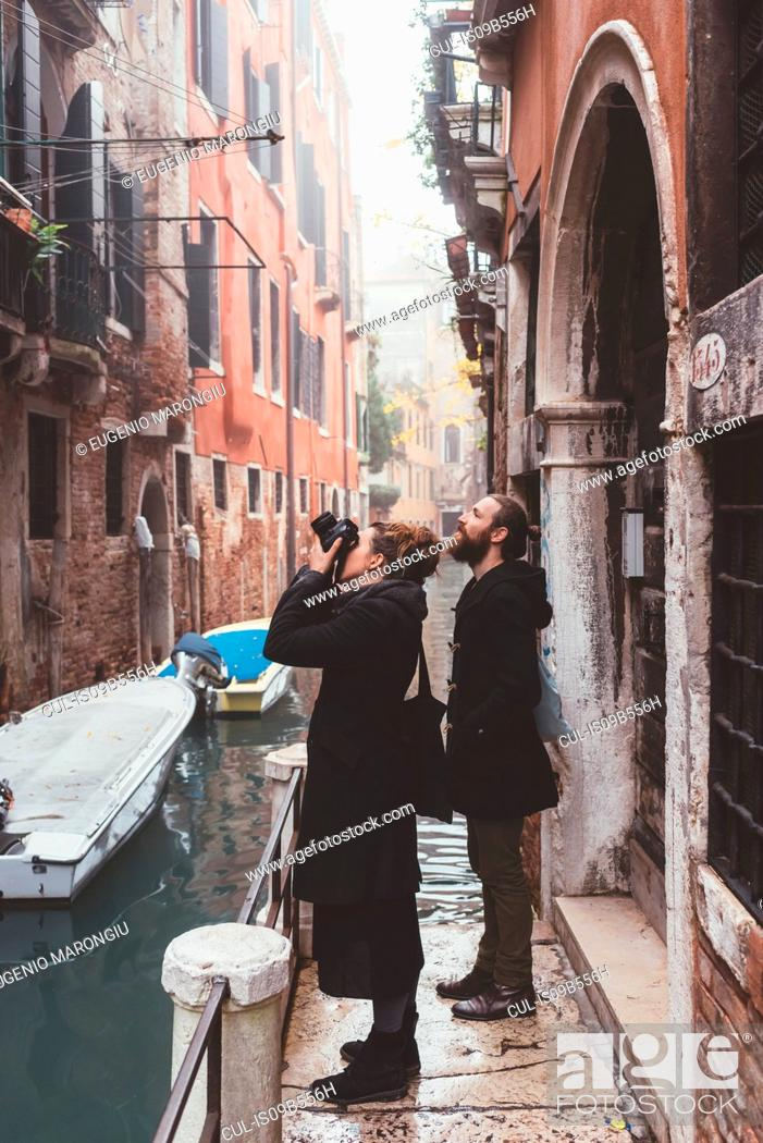 Imagen: Couple photographing building exteriors from canal waterfront, Venice, Italy.