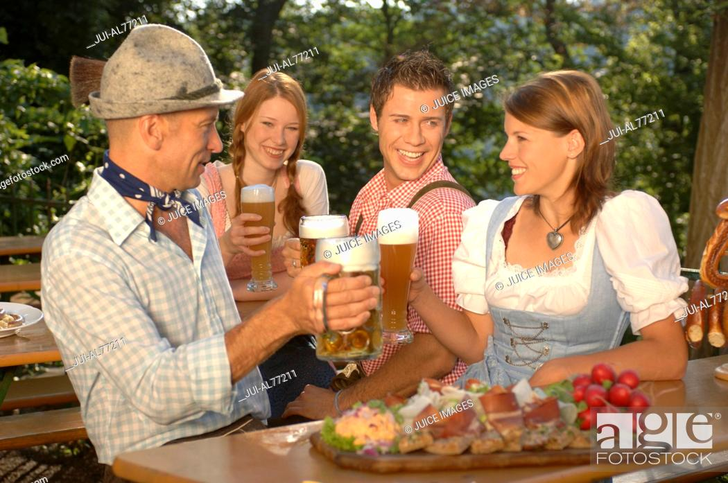 Stock Photo: View of two young couples drinking beer, beergarden, Munich, Bavaria, Germany.