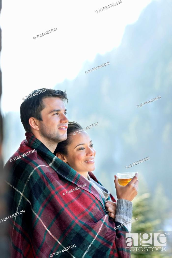 Stock Photo: Smiling couple wrapped in a blanket and drinking tea outdoors.