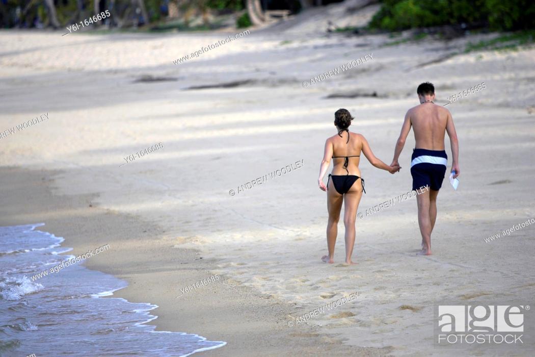 Stock Photo: Couple walk hand in hand on deserted Mae Nam beach Ko Samui island Thailand.
