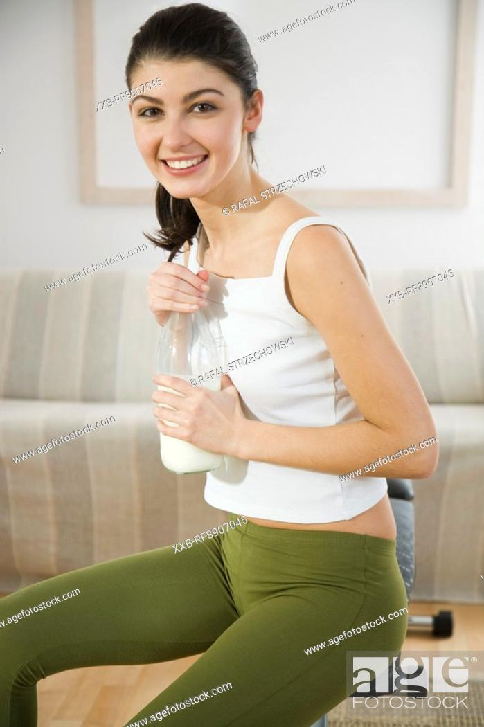 Stock Photo: young woman drinking milk.