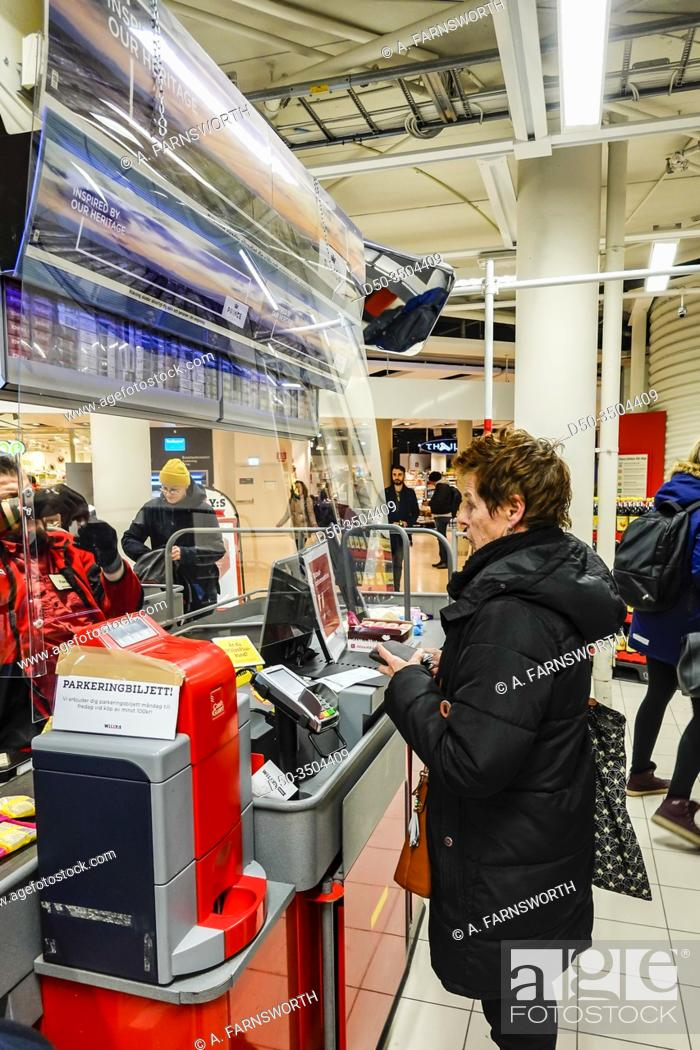 Imagen: Stockholm, Sweden April 1, 2020 Shoppers inside a supermarket in Liljeholmen stand behind plexiglas protection at the cashier.