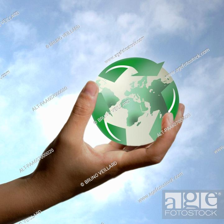 Stock Photo: Hand holding planet earth enveloped by recycling symbol.